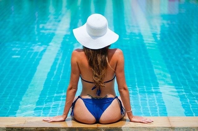 Žena v plavkách sediaca pri bazéne so strieborným náramkom na ruke
