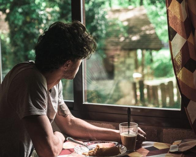 Muž sedí pri stole pod oknom, s kávou a koláčom
