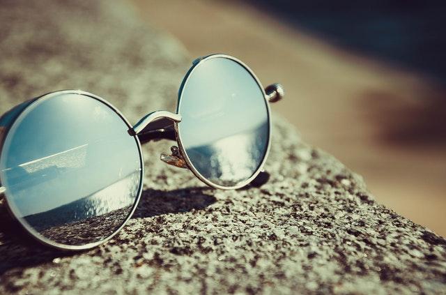Slnečné okuliare položené na betónovom múriku.jpg