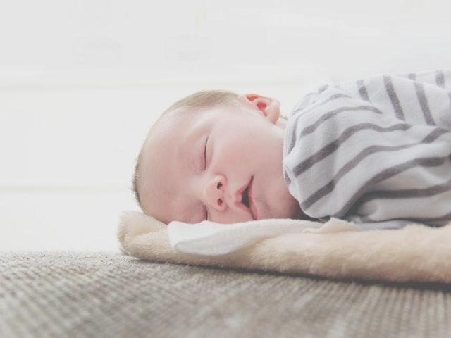 Malé bábätko, zakryté sivou dekou spí.jpg