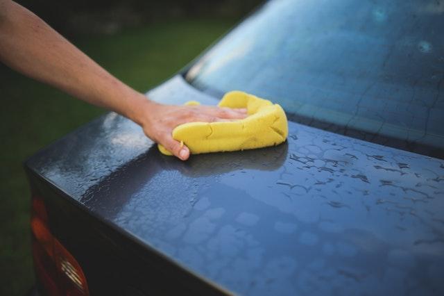 Muž umývajúci auto so žltou špongiou.jpg