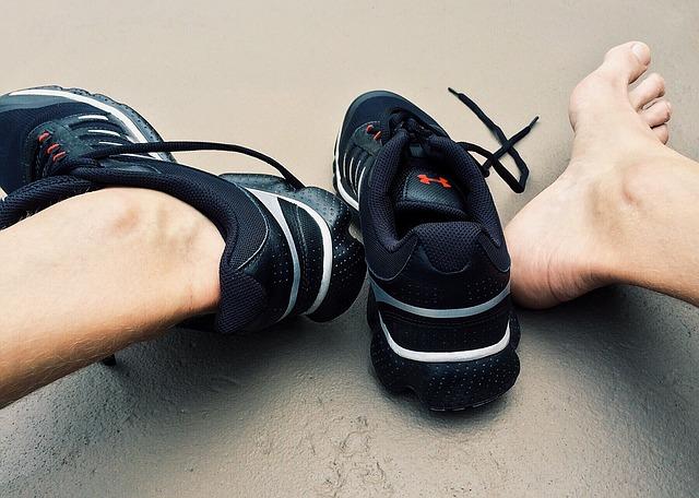 Človek sedí na zemi a vyzúva si čierne botasky.jpg